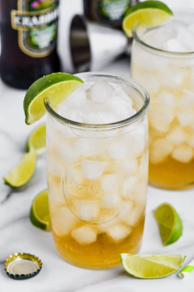 overhead angled view of a tall glass (another in the background) filled with ice and dark and stormy drink recipe, lime wedges near the base of the glass and ginger beer bottle in the background