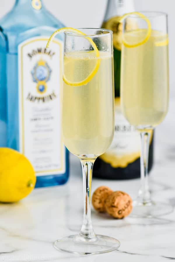 tall champagne flute filled with french 75 recipe , another champagne flue int he background, a bottle of champagne, a cork and a bottle bombay sapphire