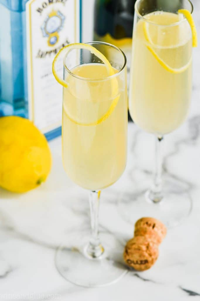 champagne flute garnished with lemon filled with a french 75 made with gin