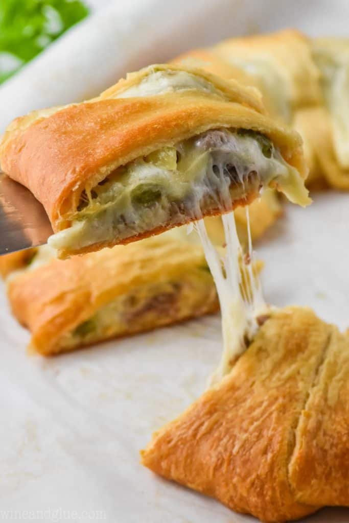 piece of a philly cheese steak crescent ring being pulled off a pan