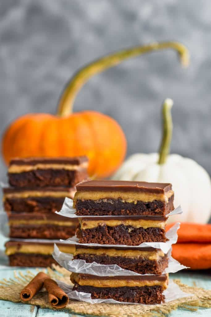 two stacks of pumpkin chocolate brownies with pumpkins in the background