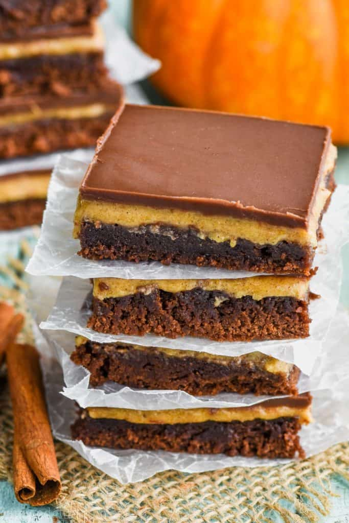 stack of pumpkin brownies with parchment paper underneath each one