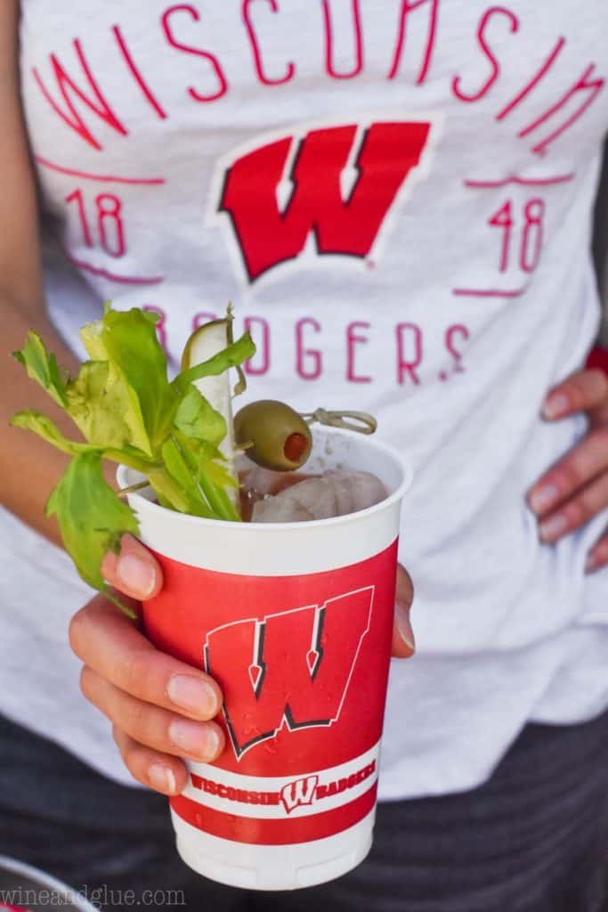 woman holding a uw cup filled with the perfect bloody mary mix
