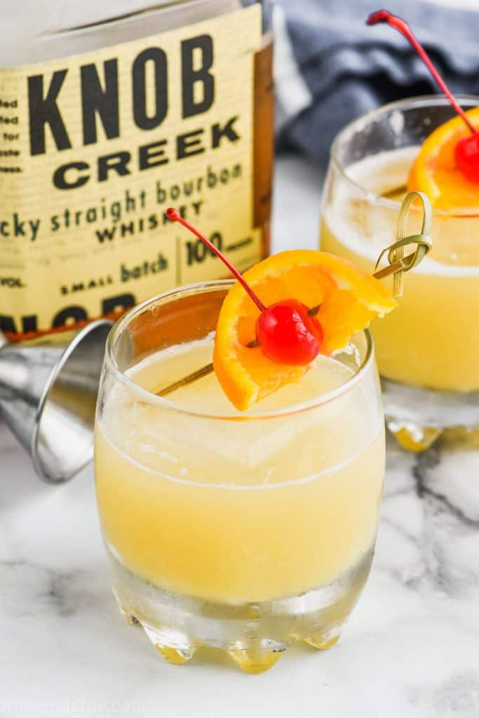 frothy glass of the best whiskey sour recipe garnished with an orange and cherry