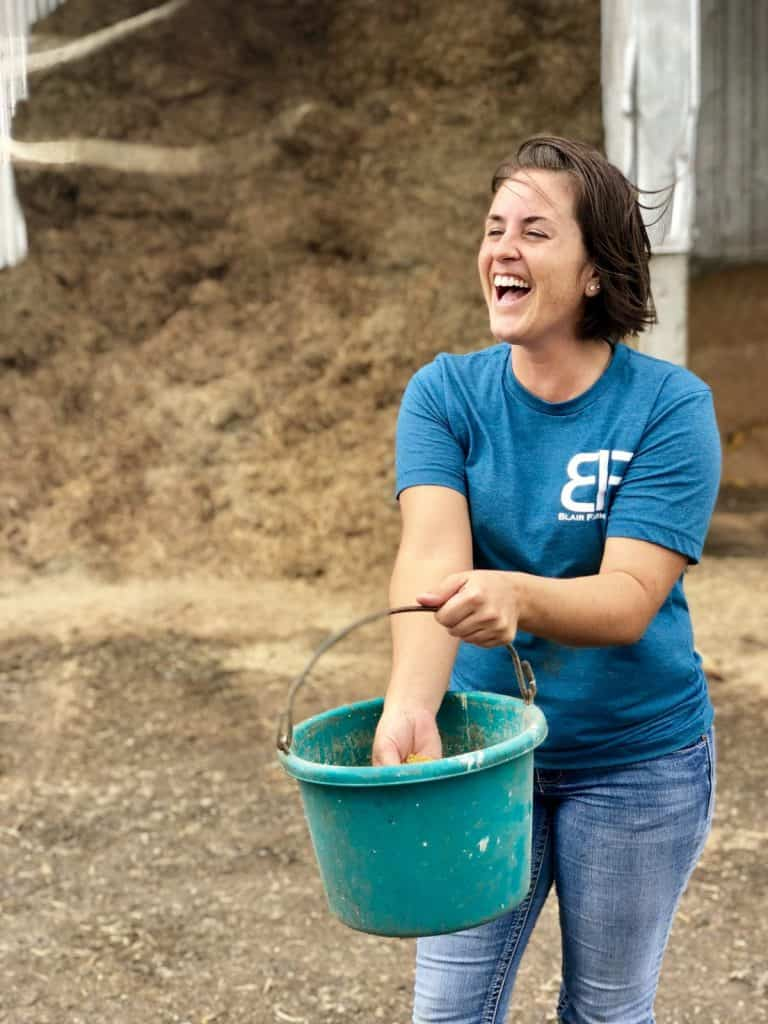 A woman holding a blue green bucket