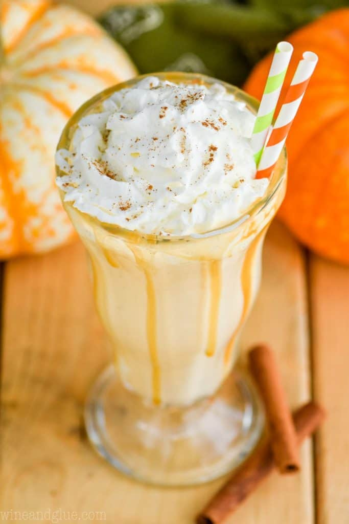 overhead view of boozy pumpkin milkshake with whipped cream and straws