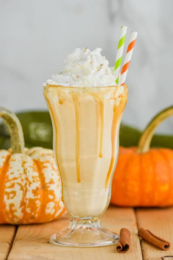 boozy pumpkin milkshake with whipped cream and straws