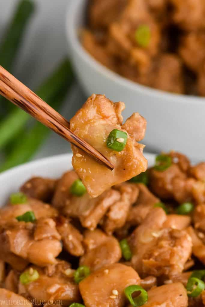 a closeup photo chopsticks holding a piece of the best bourbon chicken