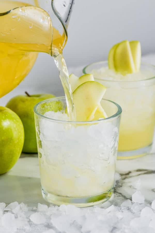 cup of caramel apple vodka punch garnished with sliced apples