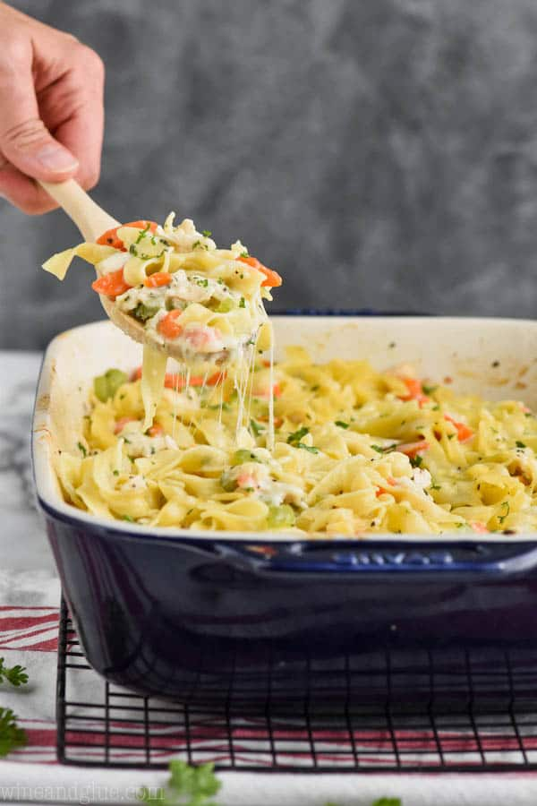 spoon digging into a cheesy chicken and noodle casserole recipe