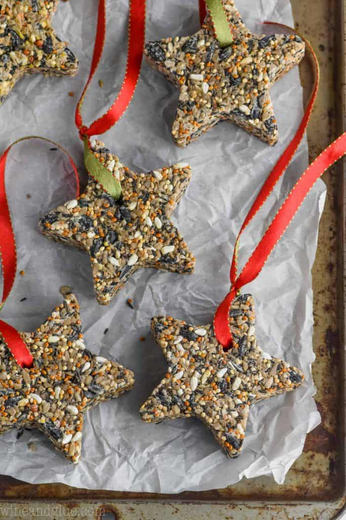 star shaped DIY bird feeders on a baking tray with a a red ribbon threaded through