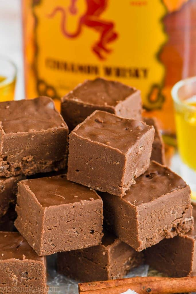 A pyramid stack of cubed Fireball Fudge with a cinnamon stick in the front and a bottle of Fireball in the back