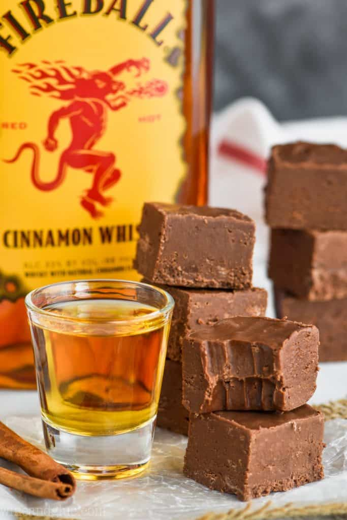 A small stack of the Fireball Fudge next to a shot glass full of fireball. The top piece has a small bite.