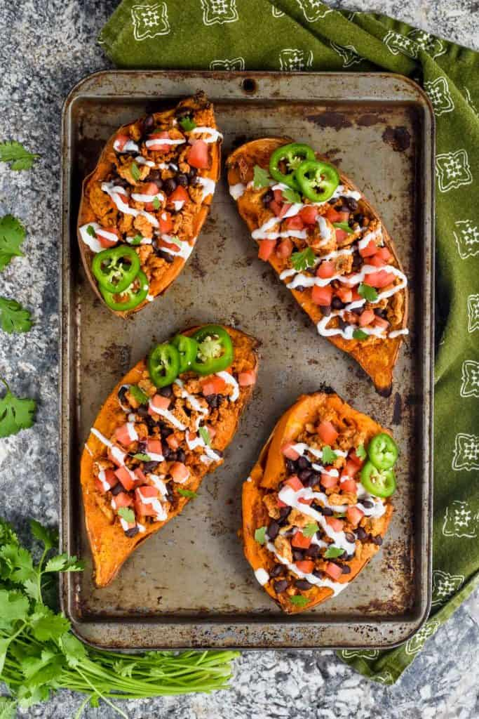 A overhead photo of four Taco Stuffed Sweet Potatoes on a sheet pan. All of then topped with sour cream and jalapenos.