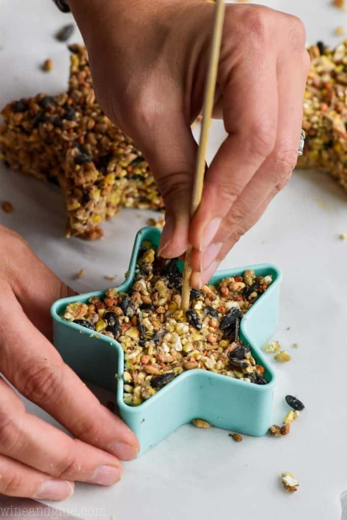 In a star shaped cookie mold, some of the bird feeder mixture is inside while having a hole created with a skewer