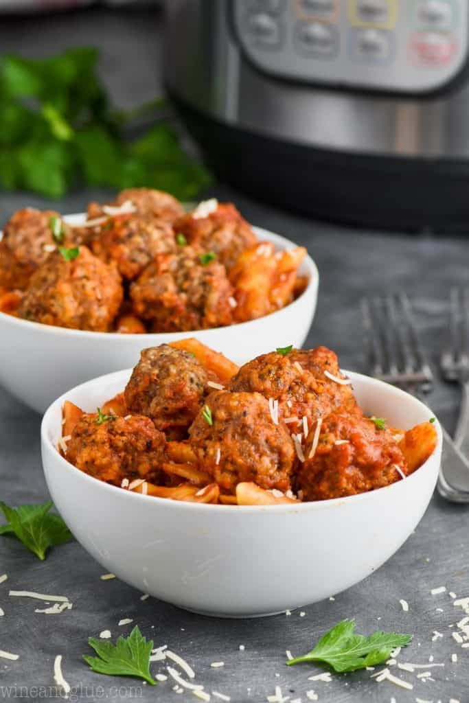 two bowls of instant pot meatballs and pasta garnished with parsley and cheese
