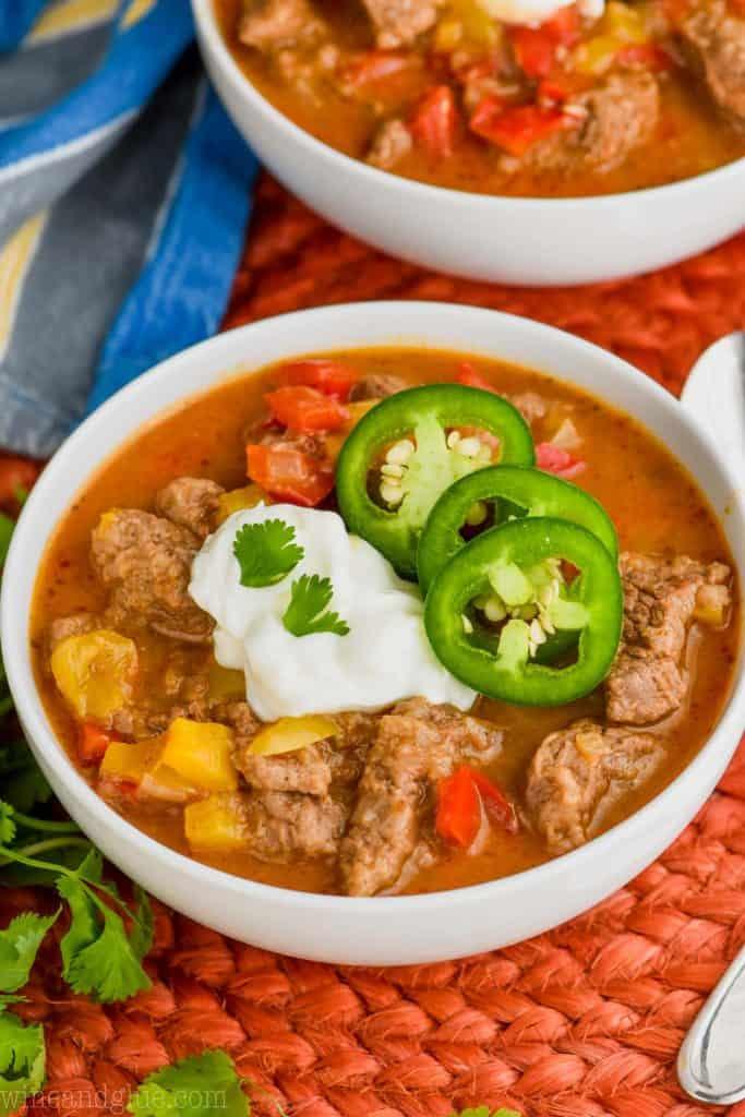 bowl of steak fajita soup recipe topped with sour cream, cilantro, and jalapeños