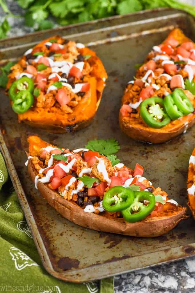 stuffed sweet potato recipe fixed like tacos on a baking sheet topped with sour cream, jalapenos, and cilantro.