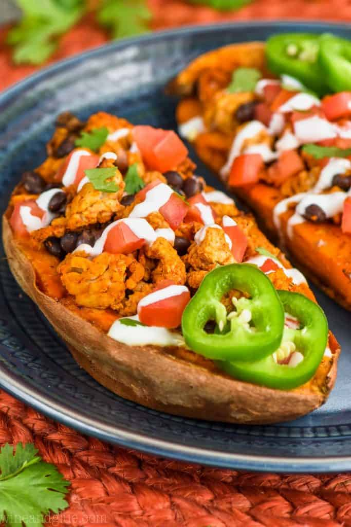 stuffed sweet potatoes garnished with taco fixings on a plate topped with sour cream, jalapenos, and cilantro