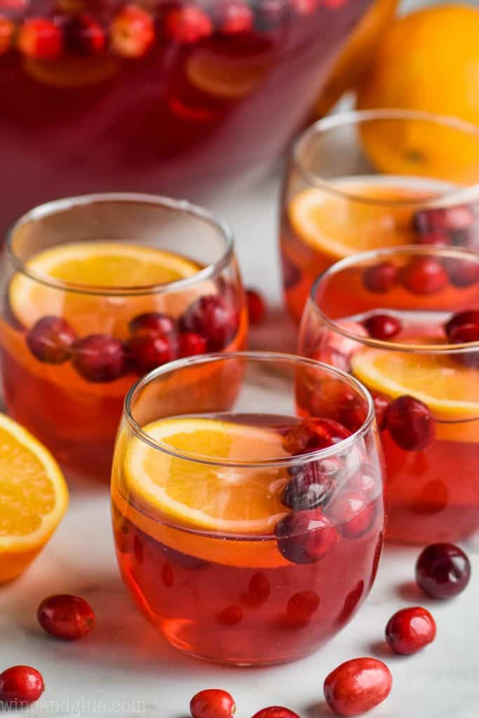 cups of christmas punch with oranges and cranberries floating in it