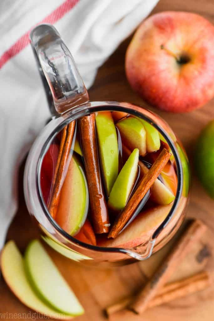overhead view of a pitcher of cinnamon sangria with sliced apples and cinnamon sticks