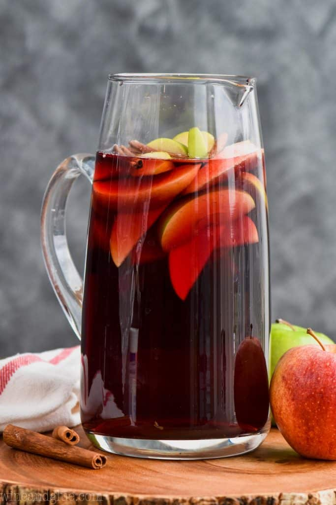 pitcher of cinnamon whiskey sangria recipe with sliced apples and cinnamon sticks