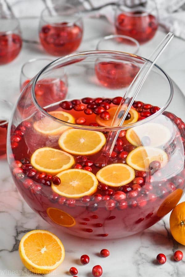 easy christmas punch recipe in a big punch bowl with oranges and cranberries