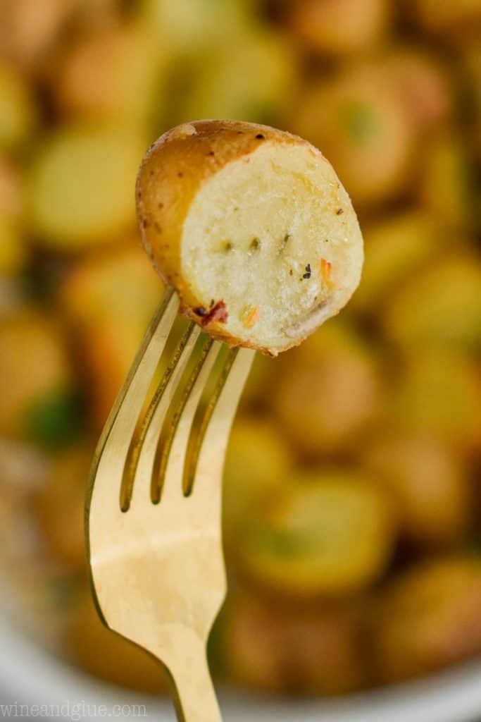 fork holding half of a roasted mini potato