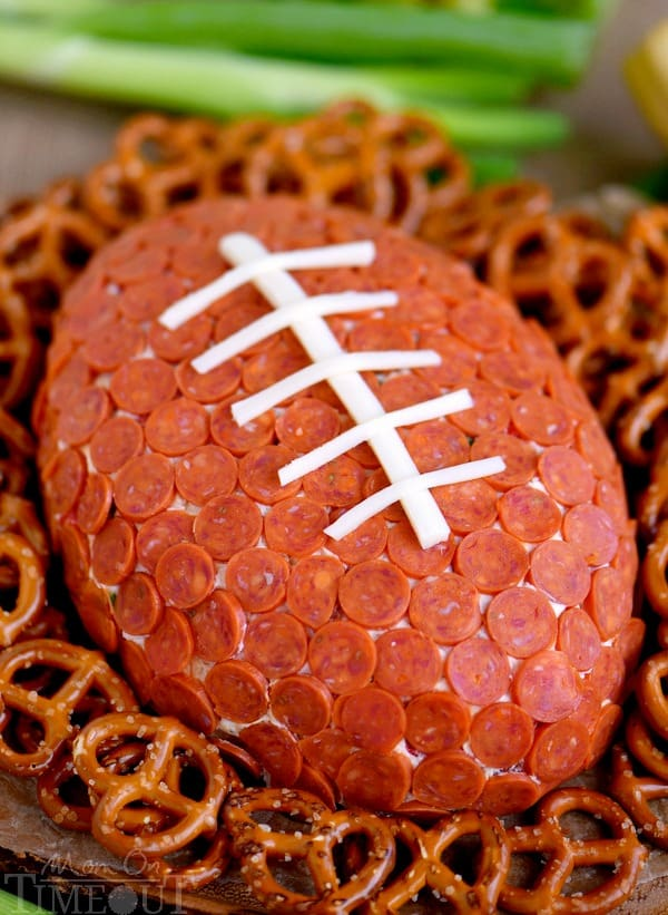 The Pepperoni Pizza Football Cheese Ball is surrounded by pretzels.