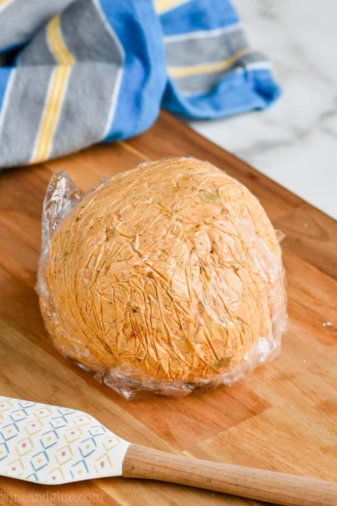 easy cheese ball recipe wrapped in saran wrap and formed into a ball