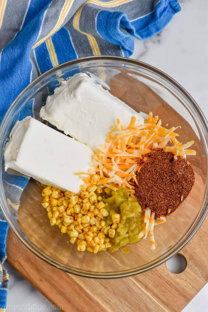 overhead view of ingredients (Cream Cheese, Corn, Taco Seasoning, Cheese, and green chilies) for easy taco cheese ball recipe