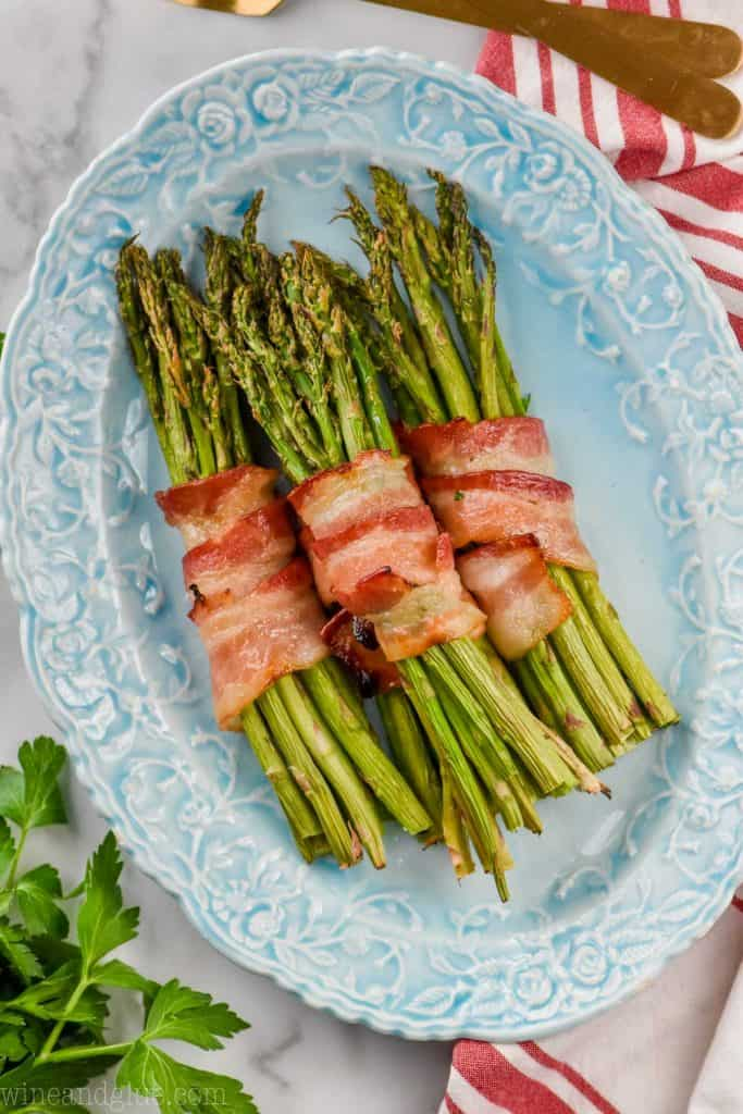 bacon wrapped asparagus prepared with brown sugar on a blue serving plate