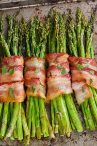 four groups of bacon wrapped asparagus baked with brown sugar on a tray