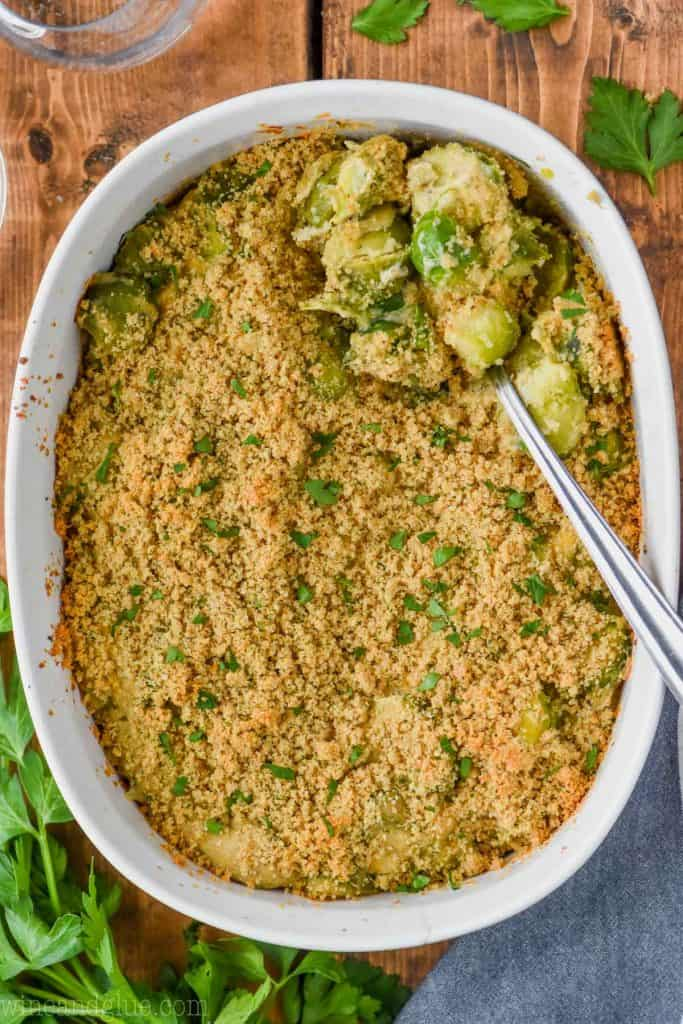 overhead one baked brussel sprouts casserole in casserole dish with spoon