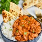 bowl of butter chicken with rice and naan