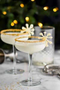 two christmas martinis garnished and in front of holiday lights