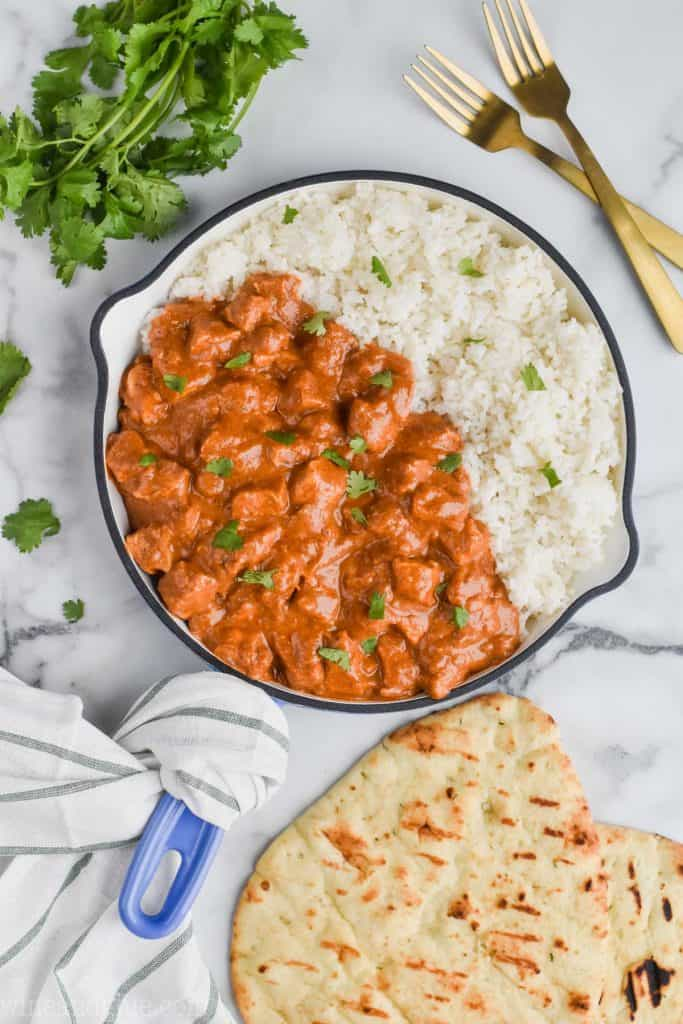 pan of creamy butter chicken with rice, cilantro and naan