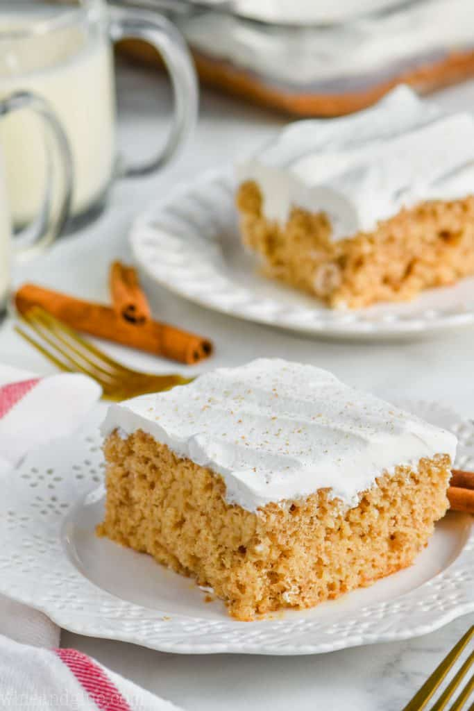 two pieces of eggnog poke cake sitting on plates