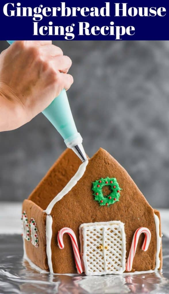 piping gingerbread icing on a built gingerbread house recipe