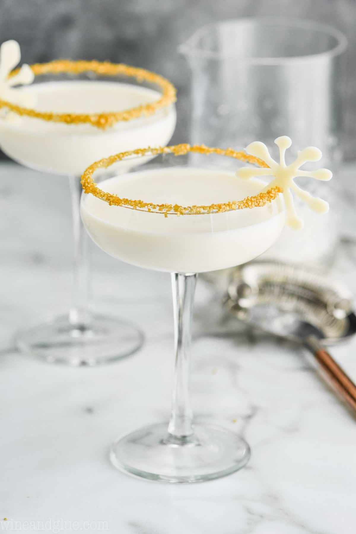 two holiday martinis for christmas in glasses garnished with gold sugar