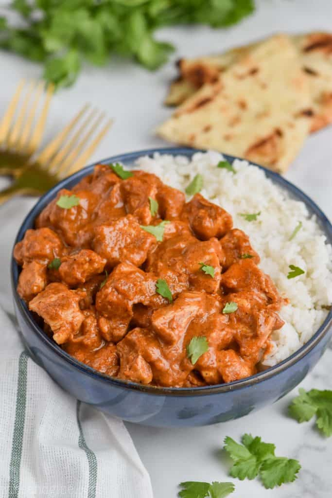 bowl of indian butter chicken recipe with rice and cilantro