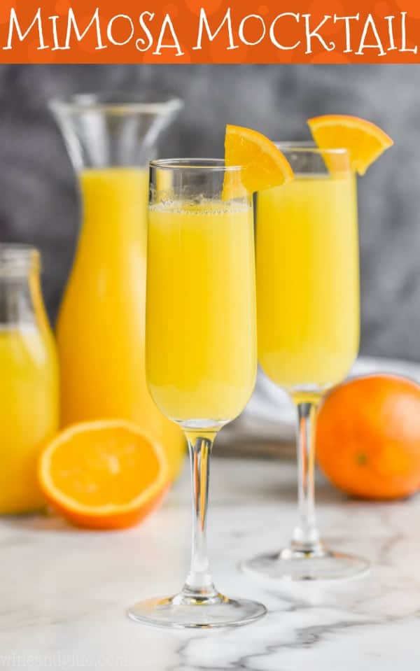 two mimosa mocktails garnished with oranges wedges