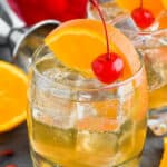 small tumbler with amaretto sour recipe garnished with an orange slice and cherry