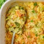 overhead view of a spoon in a casserole dish of broccoli rice casserole