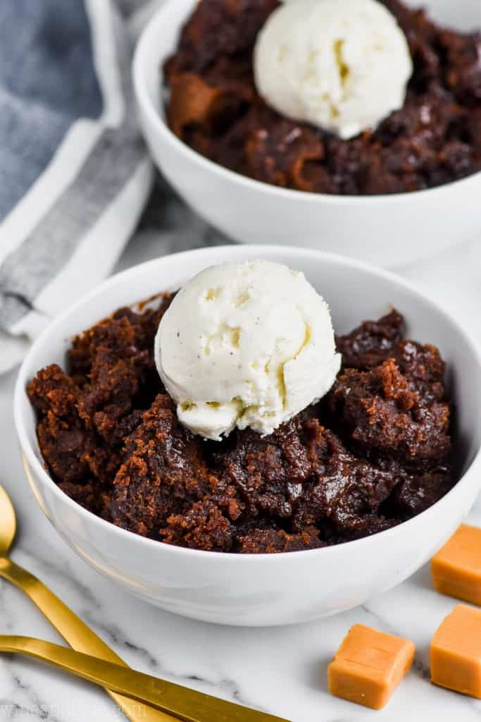 white bowl full of crock pot brownies with vanilla ice cream