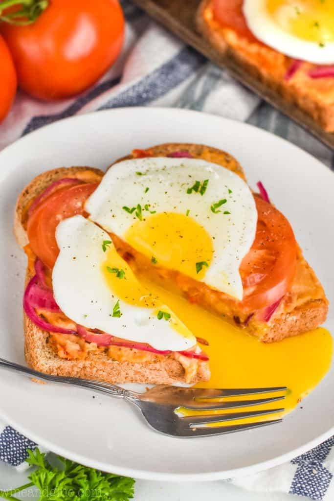 a cut open fried egg on hummus toast