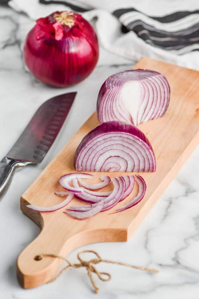 red onions being sliced as a julienne shape on a cutting board to show how to make pickled red onions