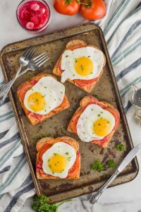 four pieces of toast with hummus and eggs on them on a baking sheet