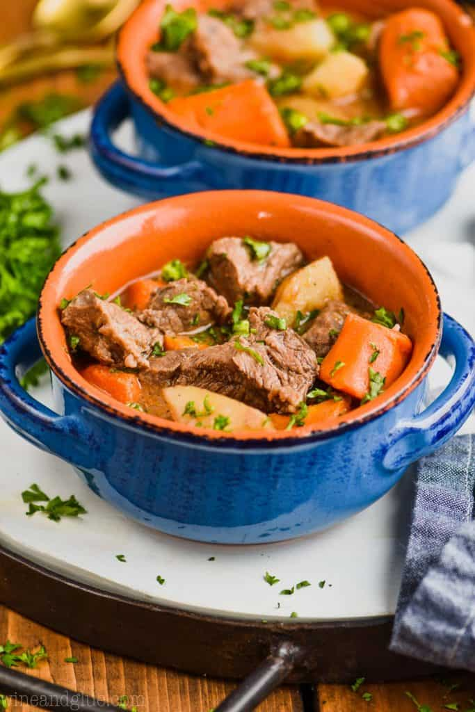 instant pot beef stew in a blue bowl garnished with parsley