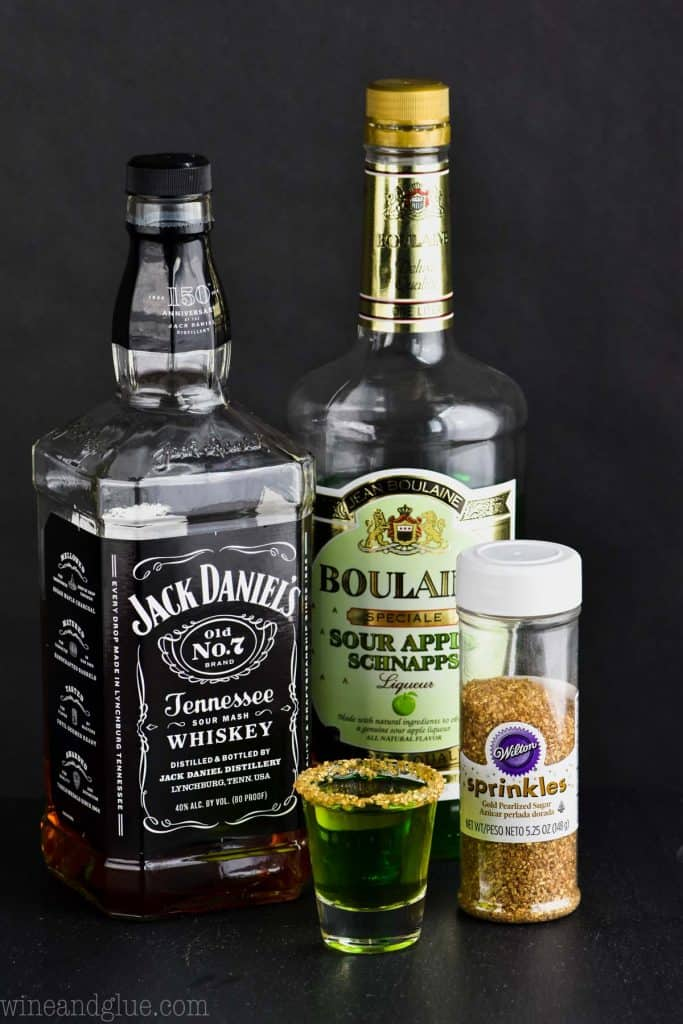 The ingredients of the Lucky Leprechaun shot which is Jack Daniel's Whiskey, Sour Apple Schnapps, and golden sprinkles.